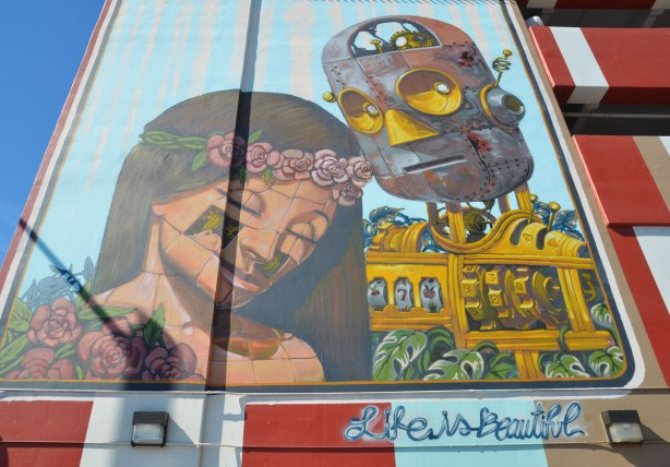 Mural of a robot man in yellow gear with a woman's head leaning against his shoulder.