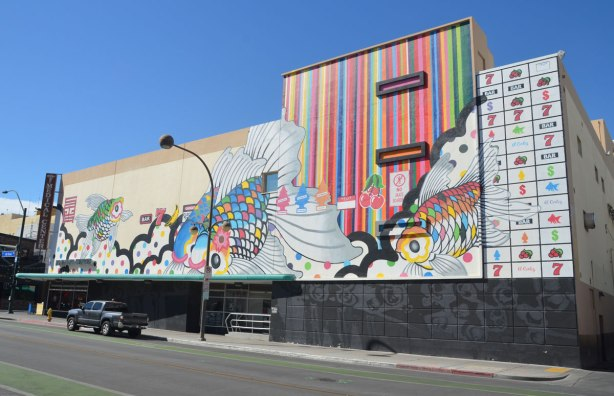 side of a three storey building on a corner in downtown Las Vegas. The upper storeys are covered with a mural, some multicolured fish, some vertical stripes
