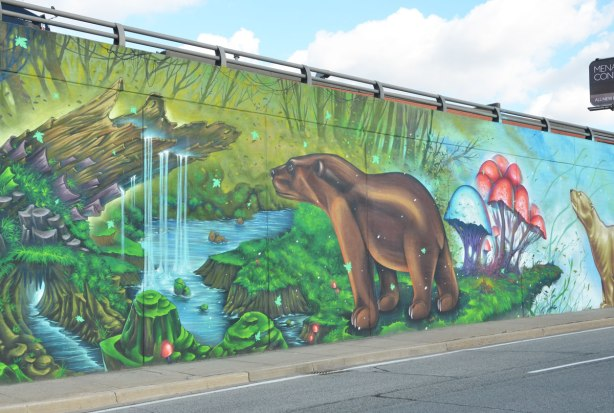 part of a large mural with an environmental theme - a brown bear stands beside a small waterfall in the midst of a lush green place