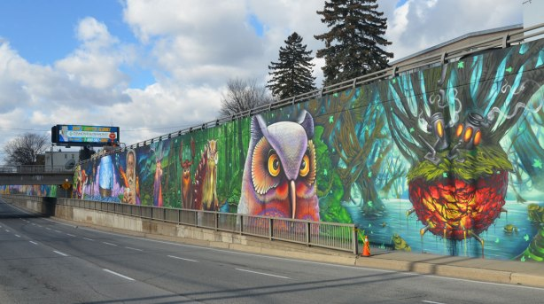 looking along a sidewalk where there is alarge mural, a very large owl is looking at you, other animals in the background.