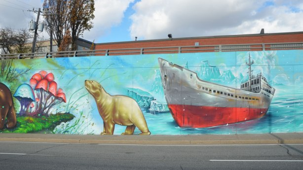 part of a mural with an environment theme, a polar bear is standing beside a red and white ship that is frozen in the arctic ice.