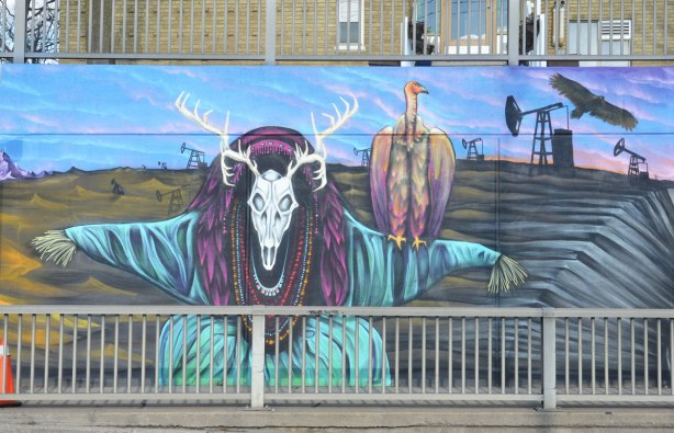 part of a larger mural on the side of an underpass, road and sidewalk in front of the photo, houses behind - a creature with a deer skull and antlers as head with a vulture sitting on its shoulder. Background scenery is dead land with an oil derrick on it.