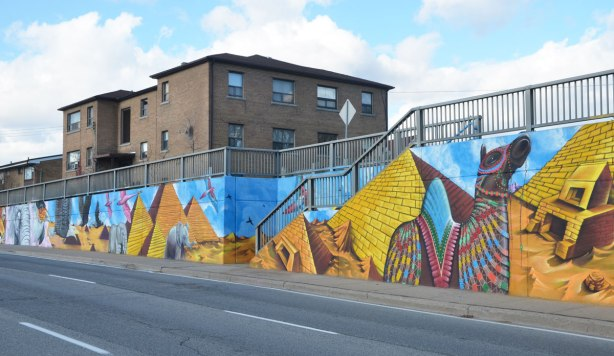 part of a larger mural on the side of an underpass, road and sidewalk in front of the photo, houses behind - looking at an angle back at the mural, Egyptian pyramids painted beside the stairs that go from the sidewalk to the houses above. Also a painted camel with a bright patterned blanket on its back.