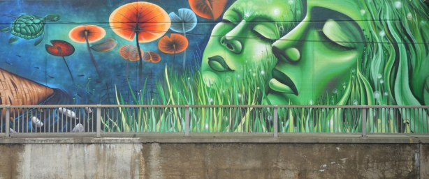 part of a larger mural on an underpass in Toronto, on Lawrence West, two woman's faces in green, eyes closed, heads slightly uplifted. long green grass around them, some orange and blue plants that look like water lily pads seen from below.