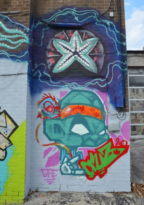 street art on the back of building. On the top is a starfish shape in blues. On the bottom is a grumpy little man with an oversized head done in teal colours. He is wearing an orange headband. GFC Cruz