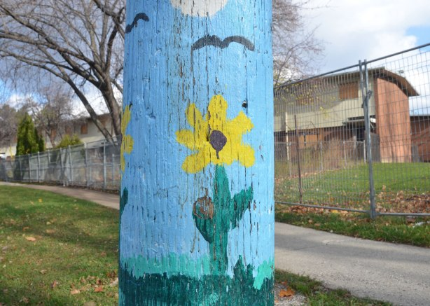 A telephone pole that has been painted on the bottom few feet. A bright blue sky with a cloud and a few birds flying, green grass and a couple of yellow flowers standing tall