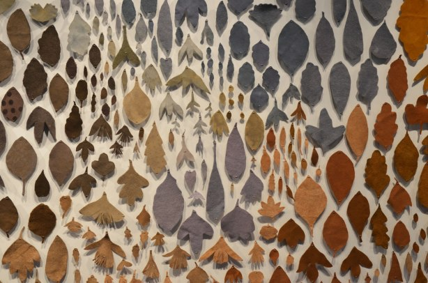 close up of A pattern of hand dyed, hand cut leaves in varying shades of yellows oranges and browns is displayed on a wall