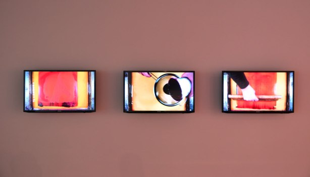 Three video screens displayed horizontally on a wall.