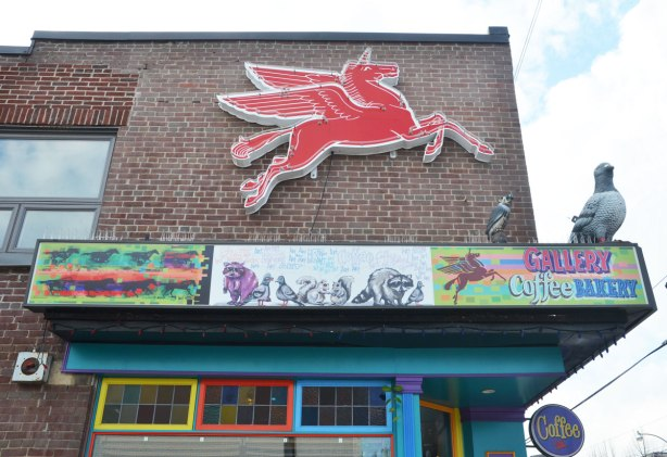 the side of the Gallery Coffee Bakery with a red winged horse sign on the upper storey of the red brick bulding. The door and window frames of the shop are painted in primary colours.