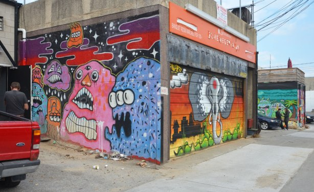 garages and walls at the back of stores and restaurants covered with street art. Pink anf purple blob like creatures and an elephant