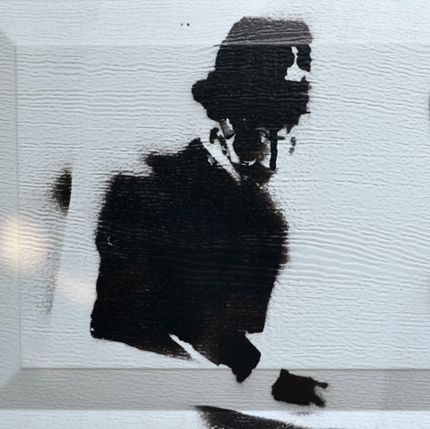 stencil graffiti in black on a white garage door. London bobby (policeman) wearing a gas mask, from the waist up