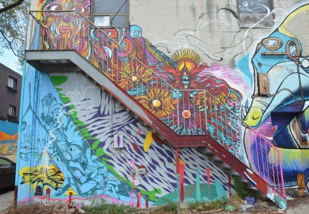 The back of a store with street art on it. A metal staircase goes diagonally up across the building. Above the stairs is a multicoloured swirly piece while under the stairs the street art in is blue and purple A campfire burns yellow in the bottom left corner.