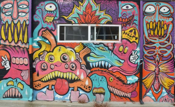 mural on a wall, with a window in the middle, many blob creatures with different number of eyes in blues, reds and purples, many with tongues sticking out, one giving a peace sign with white hand