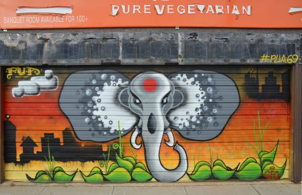 An elephant head and trunk street art painting by PUA (#PUA69) on a garage door.