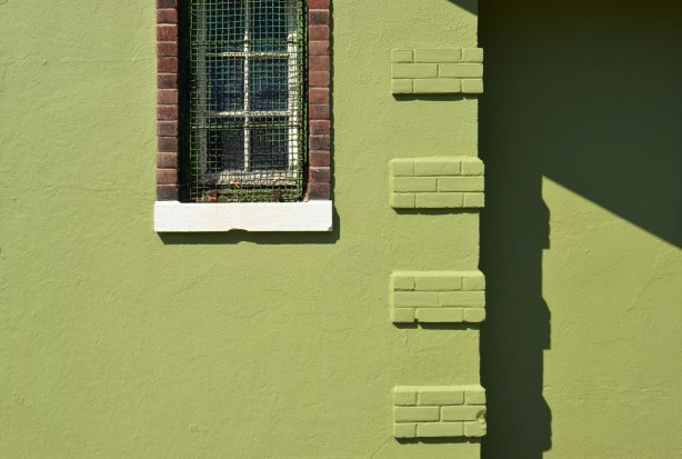 A green wall with a window taken on a sunny day when the shadows are strong. Window has brick window frame and white window sill