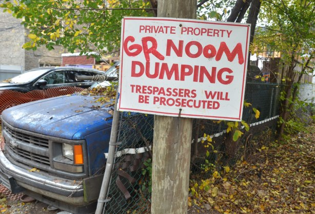 Someone hsa taken a red marker to a no dumping sign so now it reads grnoom dumping. The sign is nailed onto a post and there is an old blue truck parked behind the post.