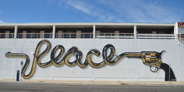 large mural of a handgun with the word peace coming out of the barrel
