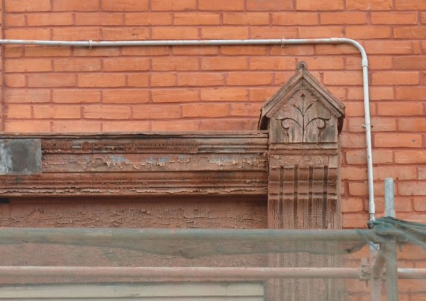 details of the carved wooden trim on a brick house being restored.