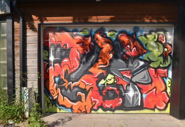 garage door covered with a street art painting of squiggly shapes in oranges and reds with dark grey background