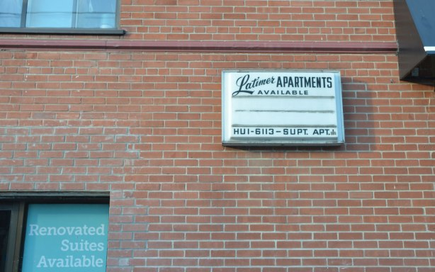 old sign on the side of an small apartment building, the Latimer Apartments, with an old Toronto phone number starting with the letters HU