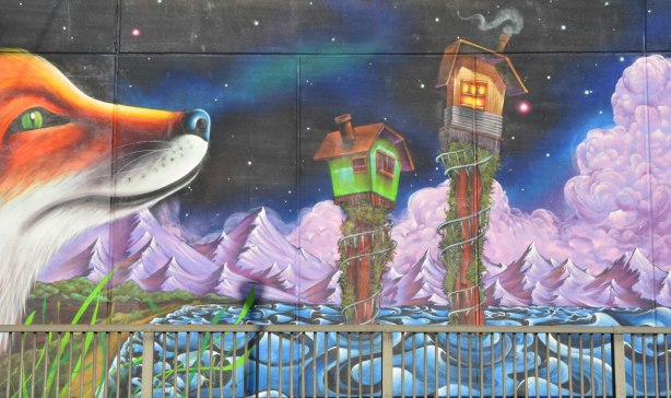 part of a mural painted on an underpass - the nose of a very large fox plus two tiny houses on stilts above turbulent water, night sky