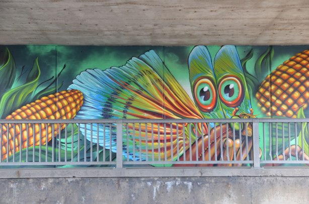 part of a mural on an underpass, under the bridge, large cobs of corn and a bright dragonfly