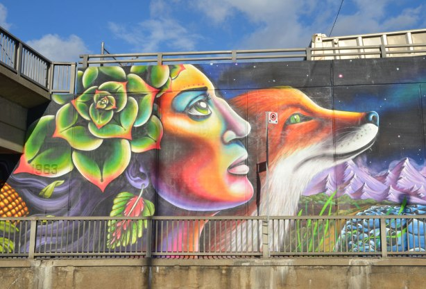 close up of part of a mural by Essencia Art Collective of a woman with a flower in her hair and a leaf shaped ear ring, mother nature like, beside a large fox.