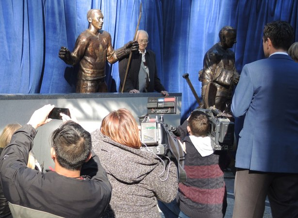 George Armstrong stands beside the statue of himself while reporters and others take pictures.