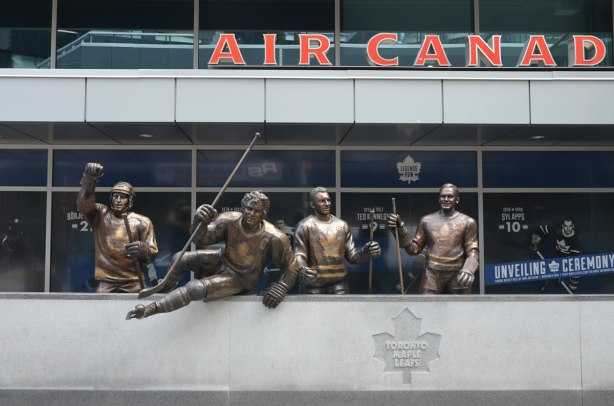 Legends Row statues, Borje Salming, Ted Kennedy and Syl Apps stand behind the boards while Darryl Sittler is jumping over the boards.