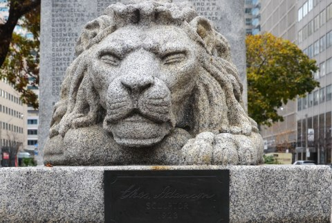 A carving of a lion in granite. It is at the base of a sculpture. A small brass plate is attached in front of the lion and it says Chas Adamson, sculptor 1923