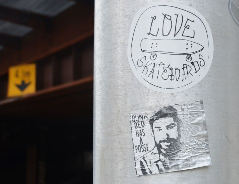 Two stickers on a metal pole beside a railway bridge. The top sticker says Love Skateboards and it has picture of a skateboard on it. The lower sticker says Bunk Bed has a Posse and a black and white drawing of a man's head is also on it.