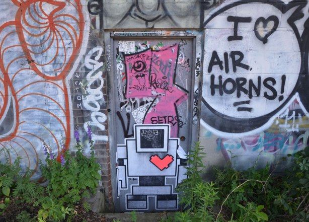 a lovebot the robot wheatpaste on a door of a building that is covered with other graffiti and street art