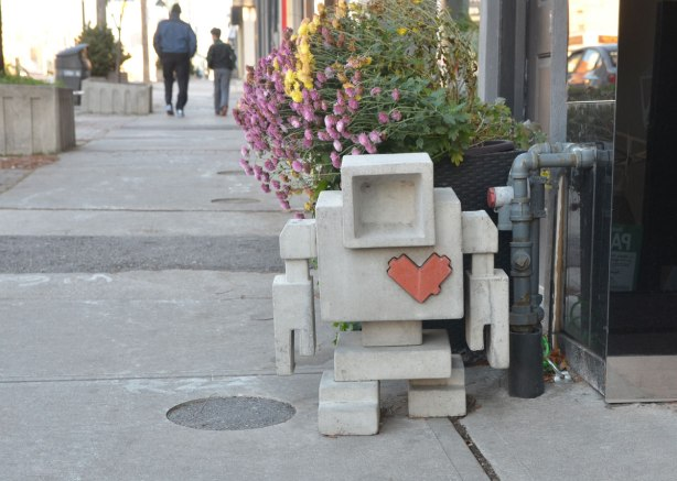 a 3D concrete lovebot stands on the sidewalk beside a store as people walk by