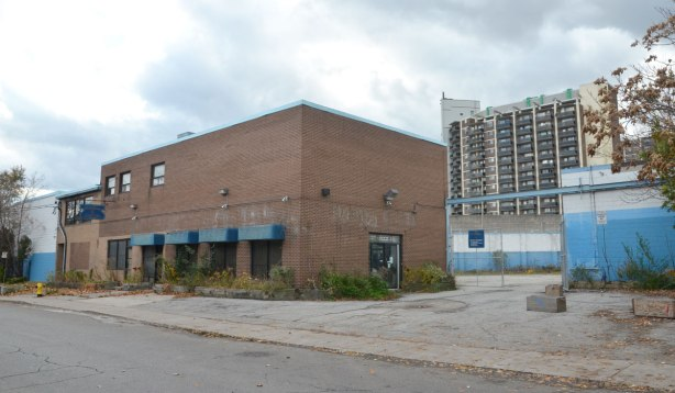 box like brick building with square awnings over the windows, large empty parking lit beside it, white and blue fence behind the parking lot, taller apartment building beyond the fence.