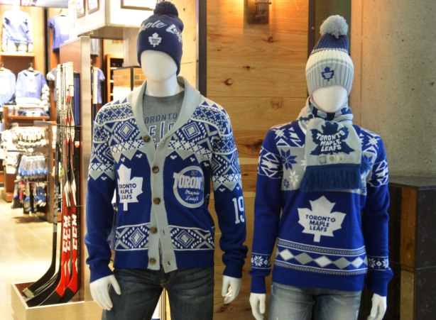 Two mannequins, one male and one female, are dressed in Maple Leaf hockey clothing.  Toques, heavy sweaters, T-shirts and scarfs, all in blue and white with the Leafs logo