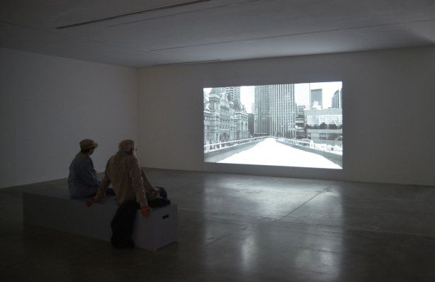 An older couple are sitting on a bench at an art gallery. They are watching a black and white film that is showing on a large screen in front of them. The image on the screen is a shot of the upper ramp at Nathan Phillips Square, looking south, in the winter with snow on the ground. There are no people in the picture on the screen.