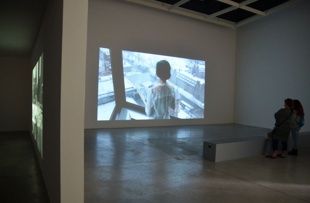 Two women are standing in the semi darkness in a room in an art gallery, watching a black and white film that is showing on a large screen in front of them. The image on the screen is the back of the upper part of a woman as she stands in front of a window in the Robarts Library in Toronto. The scene outside the window is clearly visible, winter time, University of Torotno campus. She is holding a book in her hands.