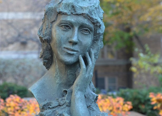 a bust of Mary Pickford, she is resting her head in one of her hands. In the background is a building along with some bushes and a tree with yellow and orange leaves.