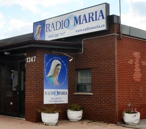 entrace to a small red brick building with a two signs, one over the door and one beside the door, for Radio Maria.