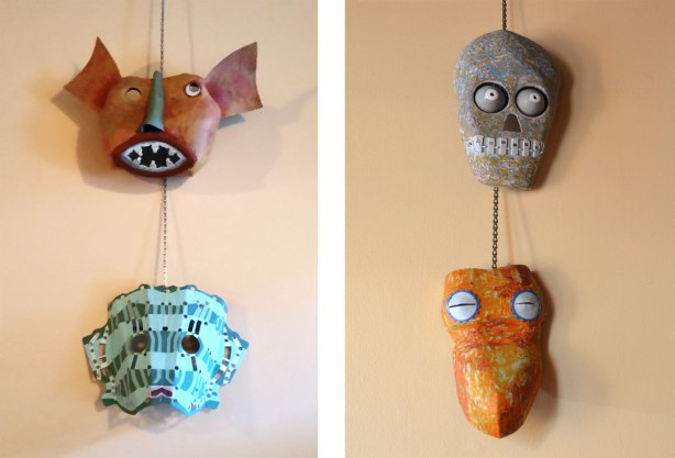 four metal masks mounted like on a wall. One looks a reddish dog and one looks like a skull. They are made of car parts.