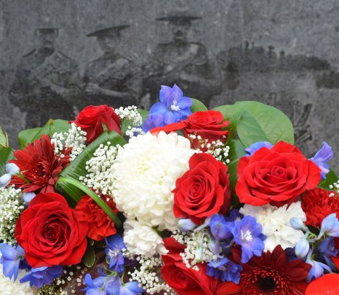 A bouquet of flowers, red roses, plus some white and blue flowers in front of a war memorial. An etching of three men in uniform, part of the memorial, is in the background.