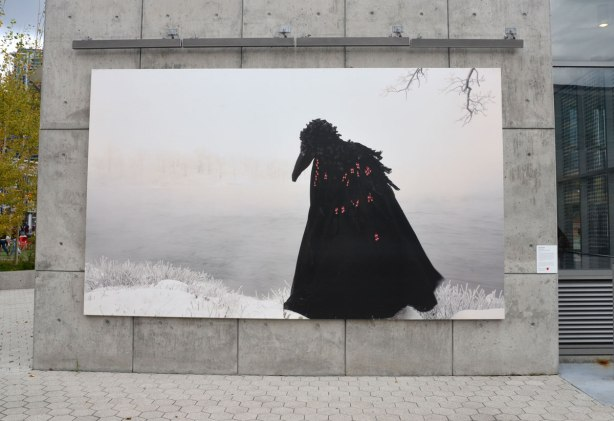 A photograph Mounted on a concrete wall outside of a person draped in a large black cape and wearing a head piece that looks like a large black bird. Photo taken outside in winter so the background is all white and grey like a foggy winter day.,