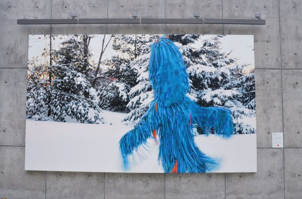 Photo of a blue furry creature taken in winter with snow covered evergreens in the background. Mounted on a concrete wall outside.