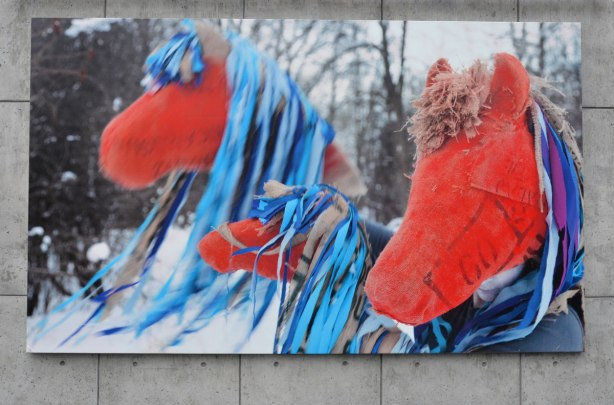 A large photograph of three red hobby horses with long blue mane, taken outside in the winter in the snow, with bare trees in the background. A mix of the real (outdoors) and the unreal (hobby horses instead of real horses). Photo is Mounted on a concrete wall outside.