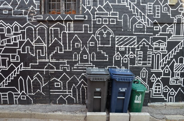 close up of part of mural, white line drawings of a city scene, lots of houses and other buildings, on a black background on the side of a house. Small window as well as three trash bins are in the picture.