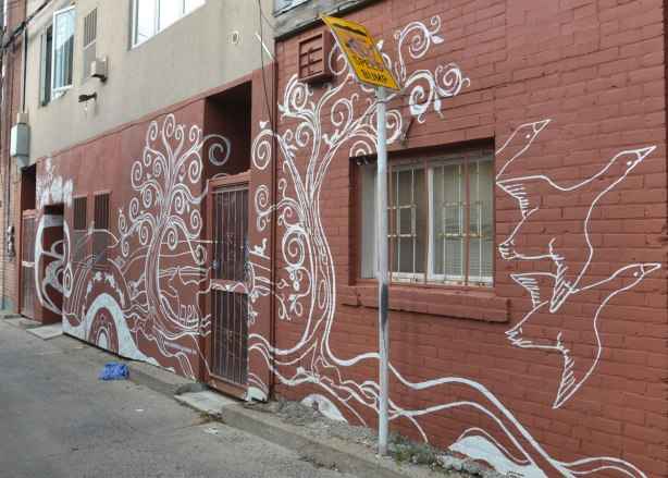 a mural on the back of a building in a laneway. Brown background, white line drawing of different animals and shapes, two geese or ducks flying to the right, a tree painted beside a doorway.