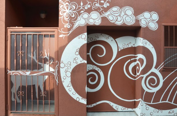 mural by Monica on the Moon, white line drawings on brown background, across the back of a building in a laneway - a deer behind a metal gate, spirals and swirls