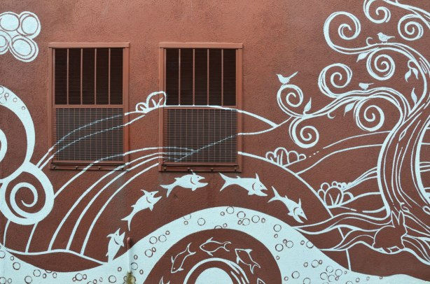 part of a mural by Monica on the Moon, white line drawings on brown background, across the back of a building in a laneway - jumping fish, a tree