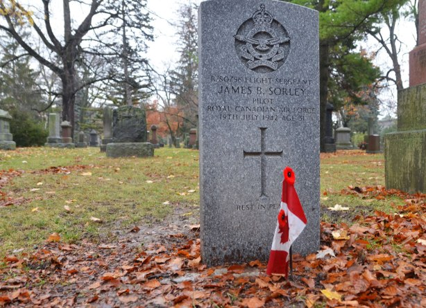 A small Canadian flag with two poppies pinned to it. The flag is inserted into the ground in front of a tombstone in a cemetery. The stone is a veterans stone, with air force insignia at the top and a cross at the bottom. In the middle is the information for the pilot who died during the war.