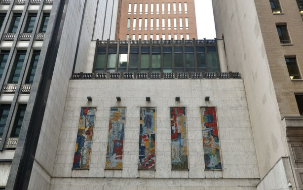 Five vertical panels of mosaics above the entrance of a downtown building, much taller buildings are on either side of it and behind it. Bell Canada building on Adelaide West, mosaics by York Wilson, communication theme public art